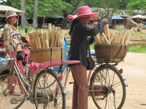 Vendor with bamboo tubes of krahlan in basket